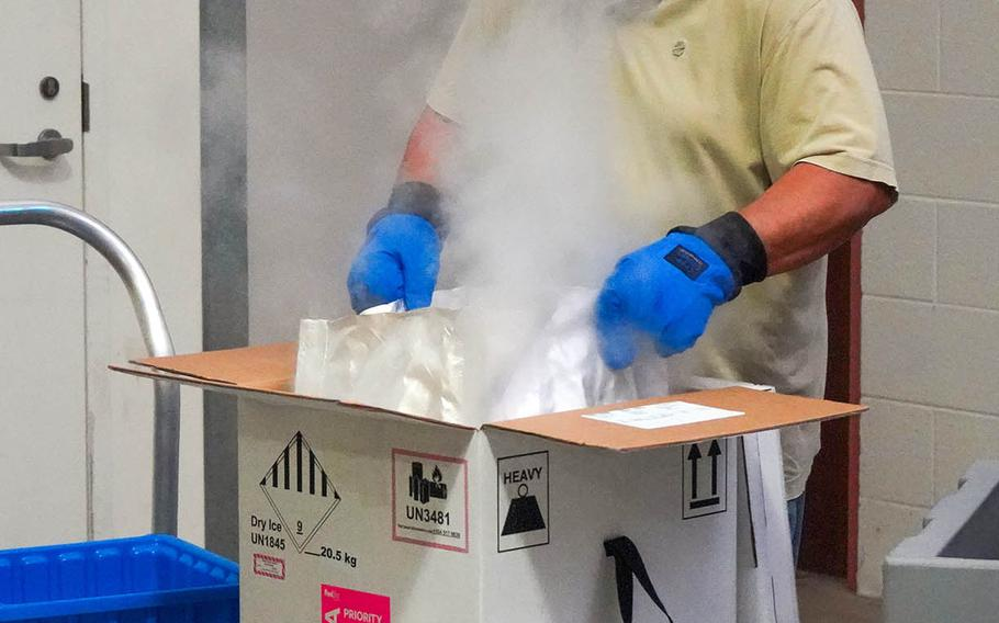 Norberto Seda-Ortiz, a member of Tripler Army Medical Center's Logistics Division, unpacks the Hawaii facility's first shipment of coronavirus vaccine from its dry-ice container, Tuesday, Dec. 15, 2020.