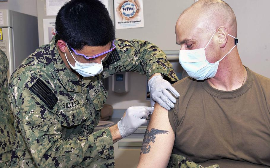 Navy Hospitalman Roman Silvestri administers a coronavirus vaccine to Cmdr. Joseph Kotora at Naval Medical Center Portsmouth, N.H., on Dec. 15. Vaccines are coming soon to six installations in Japan, U.S. Forces Japan announced Dec. 20.