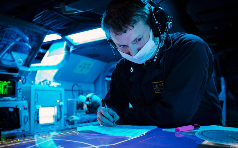 U.S. Navy Lt. Christopher Baier, from Cheboygan, Mich., logs anti-submarine warfare reports while standing watch aboard the guided-missile destroyer USS John S. McCain in the Philippine Sea on Dec. 16, 2020.