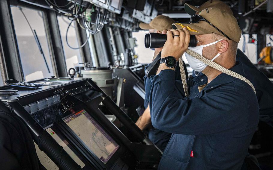Cmdr. Ryan T. Easterday, commander of the USS John S. McCain, scans the horizon in the South China Sea from the pilot house on Dec. 22, 2020.