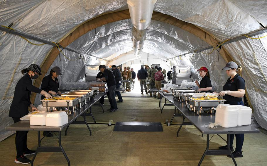 Sailors and airmen prepare food for personnel in isolation due to coronavirus restrictions at Naval Air Facility Misawa, Japan, on April 1, 2020.