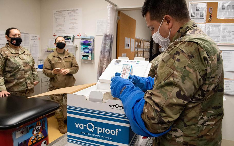 Staff Sgt. Daniel Monzon-Kazhe, 374th Medical Group, holds a box of Moderna COVID-19 vaccines at the immunization office on Yokota Air Base, Japan, Dec. 26, 2020.