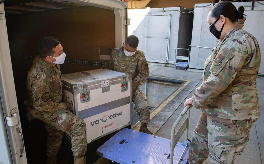 Members of the 374th Medical Group load the first shipment of Moderna COVID-19 vaccines onto a cart at Yokota Air Base, Japan, Dec. 26, 2020.
