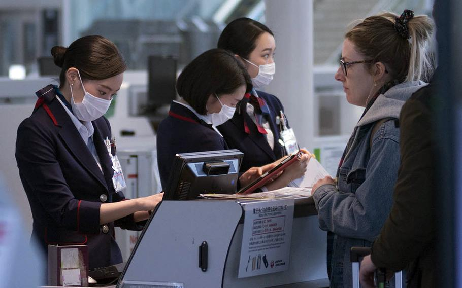 Airline ticket agents at Haneda Airport process passengers for boarding on  March 18, 2020. Japan is imposing a temporary ban on incoming nonresident foreigners starting Dec. 28, 2020.