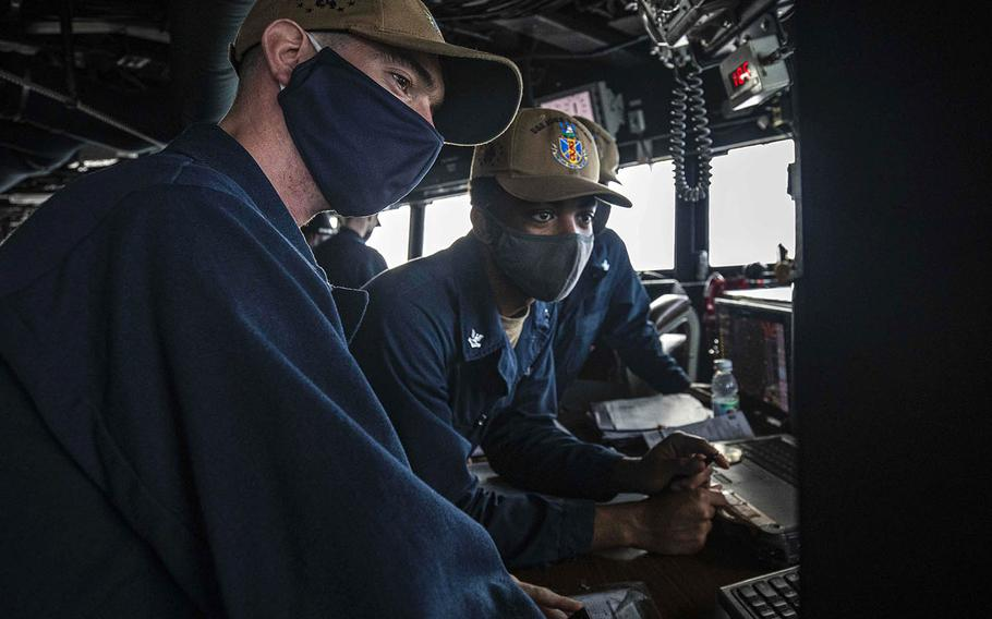 Navigator Lt. j.g. Daniel Feeney, left, from Old Greenwich, Conn., and Quartermaster 2nd Class Asah Favors, from Suffolk, Va., review the USS John S. McCain's course in the South China Sea on Dec. 22, 2020.