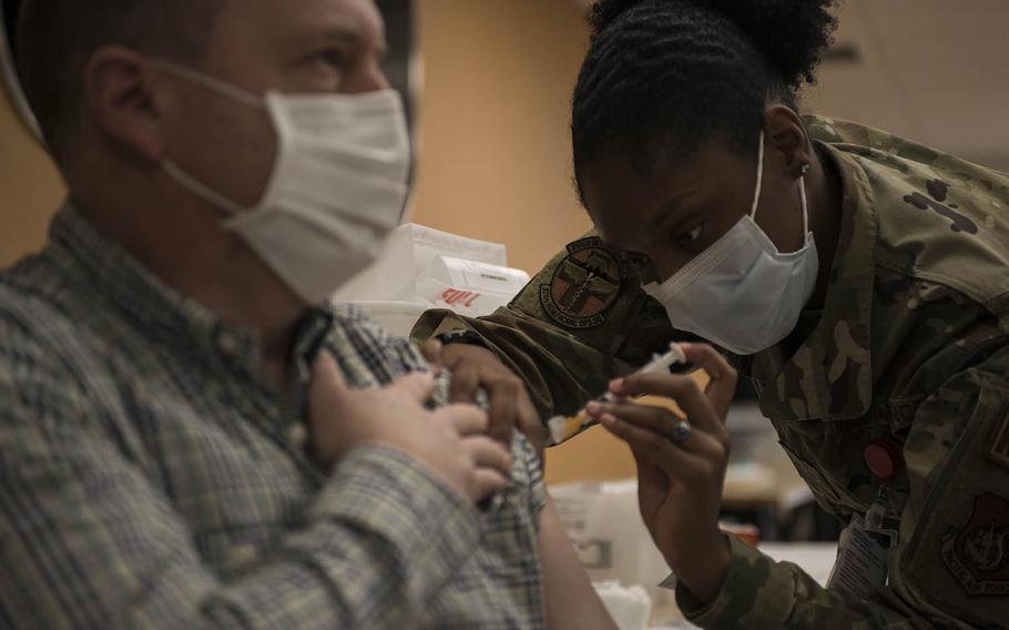 Air Force Staff Sgt. Shakeyla Moses, 25, from Columbus, Ga., administers the Moderna coronavirus vaccine to Col. Dane Campbell, medical group deputy commander at Yokota Air Base, Japan, on Monday, Dec. 28, 2020.