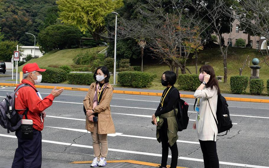 A volunteer guide provides a tour to visitors masked and socially distanced against the coronavirus at Yokosuka Naval Base, Japan, on Nov. 8, 2020.