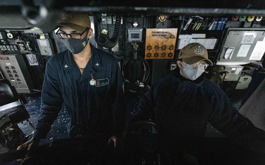 Boatswain's Mate 3rd Class Jonni Melo, left, from Bronx, N.Y., and Boatswain's Mate 3rd Class Nicole Zapata, from Tampa, Fla., stand watch in the pilot house aboard USS John S. McCain in the Taiwan Strait on Wednesday, Dec. 30, 2020.