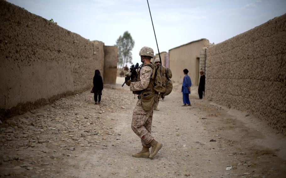 """A U.S. Marine with Task Force Southwest moves through a village during a patrol near Bost Kalay, Afghanistan, in June 2018. The Trump administration says it has intelligence that China offered to pay militants in Afghanistan to attack American troops, but unnamed government officials are dismissing the evidence against Beijing as """"very thin,"""" U.S. media reports published in December 2020 say."""