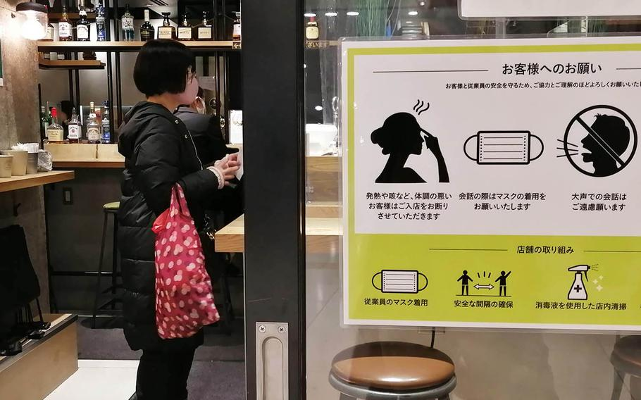 Signs in a shopping area near Yokohama Station urge passersby to observe coronavirus prevention measures on Dec. 21, 2020.