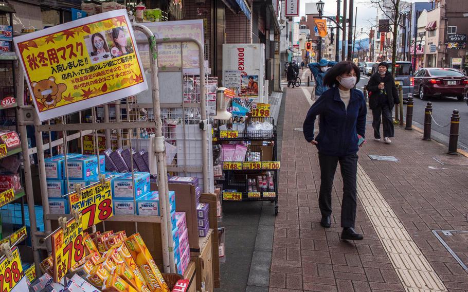 Pedestrians wearing masks as safeguards against the coronavirus walk along a street in Fussa, western Tokyo, Japan, on Jan. 5, 2021.