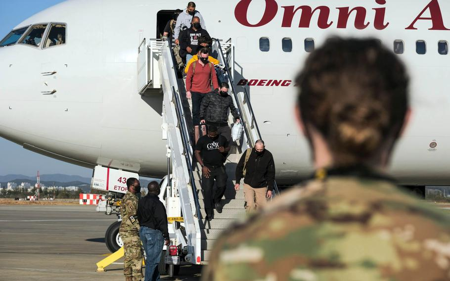 U.S. service members and their families exit the Patriot Express at Osan Air Base, South Korea, Wednesday, Oct. 28, 2020.