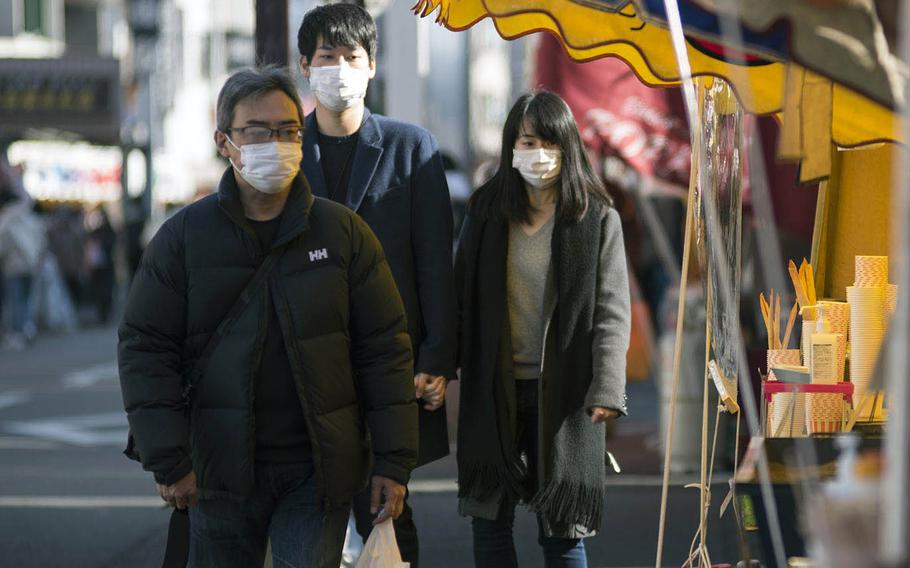 Visitors to Kawasaki-Daishi temple in Kanagawa prefecture, Japan, wear masks while strolling past souvenir and food stands on Jan. 4, 2021.