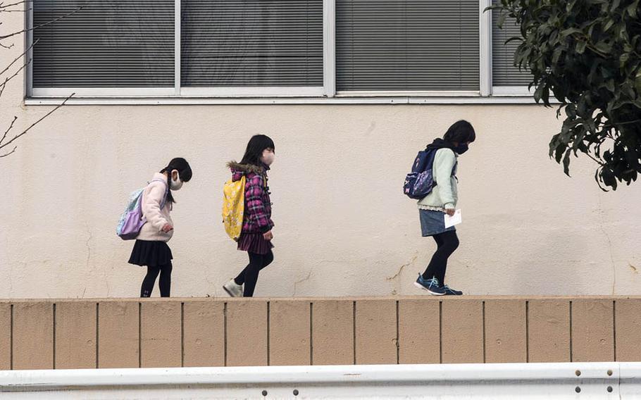 Children masked against the coronavirus make their way along a street in Fussa, Japan, on Jan. 5, 2020.