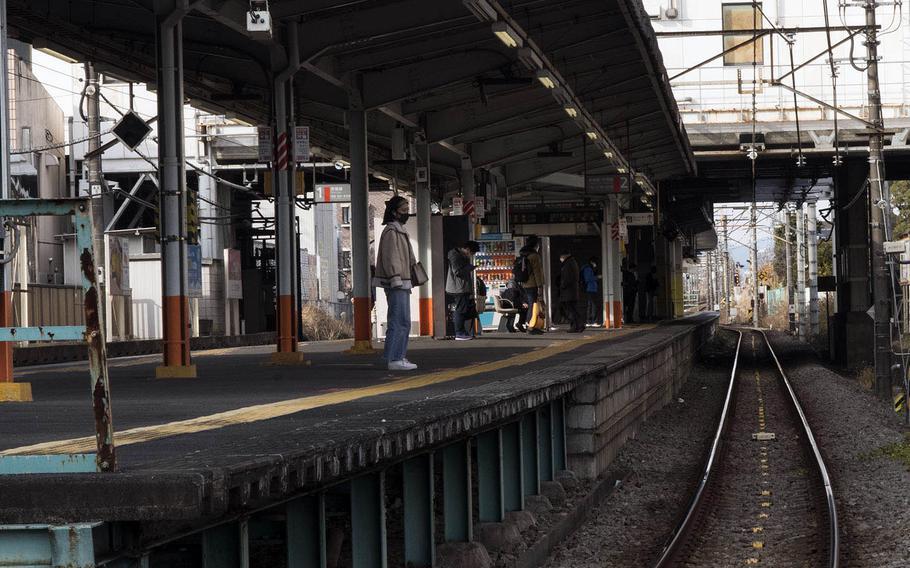 A lone, masked traveler waits for a train in Fussa, near Yokota Air Base, Japan, Jan. 5, 2020.