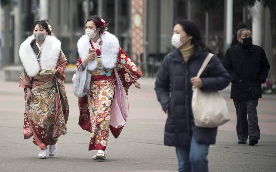 Young women in Yokohama, Japan, dressed for the Japanese coming-of-age ceremony, wear masks as protection against the coronavirus, Monday, Jan. 11, 2021.