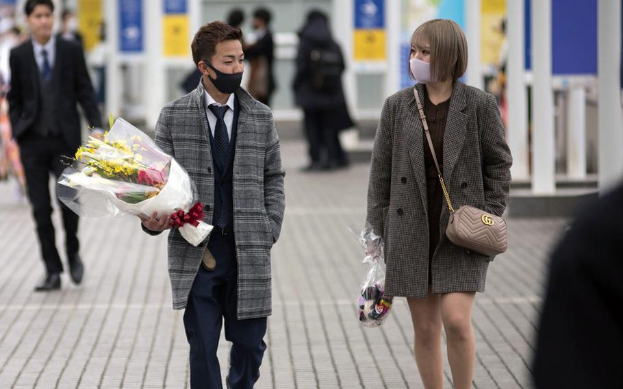 Yokohama pedestrians wear masks en route to Japanese coming-of-age ceremonies, Monday, Jan. 11, 2021.