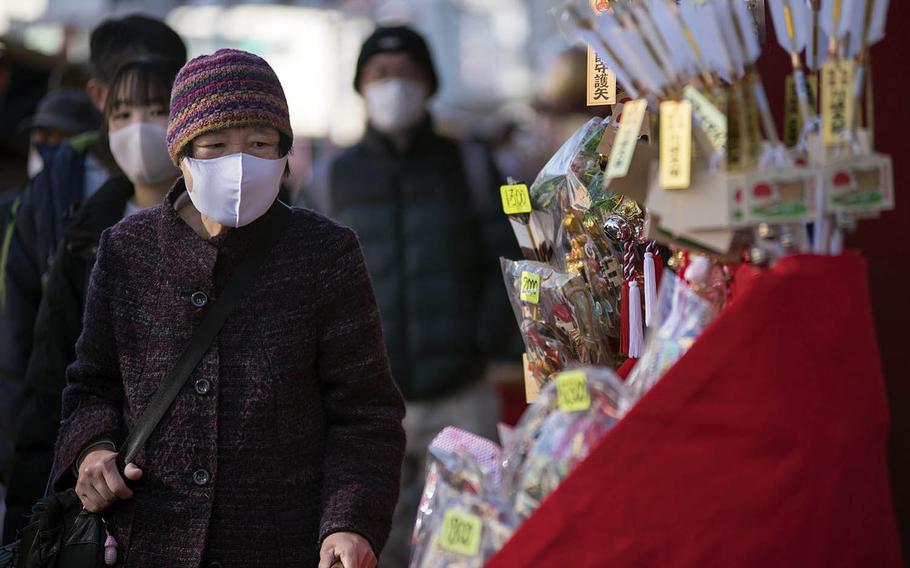 People wear masks early this month while visiting Kawasaki-Daishi, a Buddhist temple in Kawasaki, Japan.