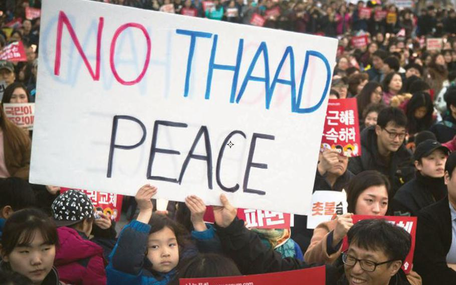 A child helps hold up a sign protesting the U.S. military's Terminal High Altitude Area Defense, or THAAD, missile-defense battery, during a gathering at Gwanghwamun Square in Seoul, South Korea, March 11, 2017.
