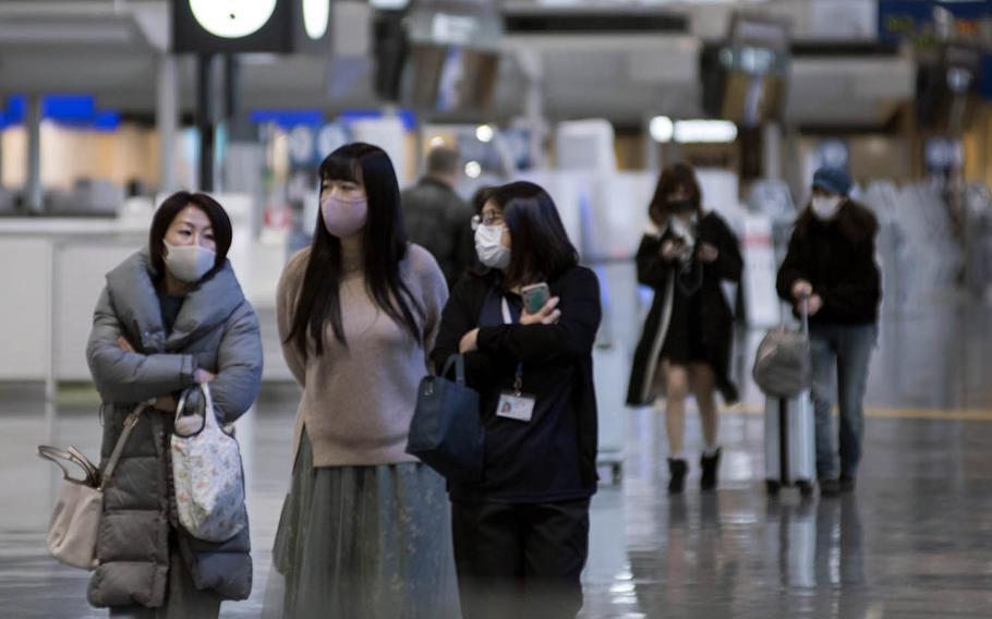 Travelers wear masks inside a terminal at Narita International Airport outside Tokyo, Jan. 15, 2021.