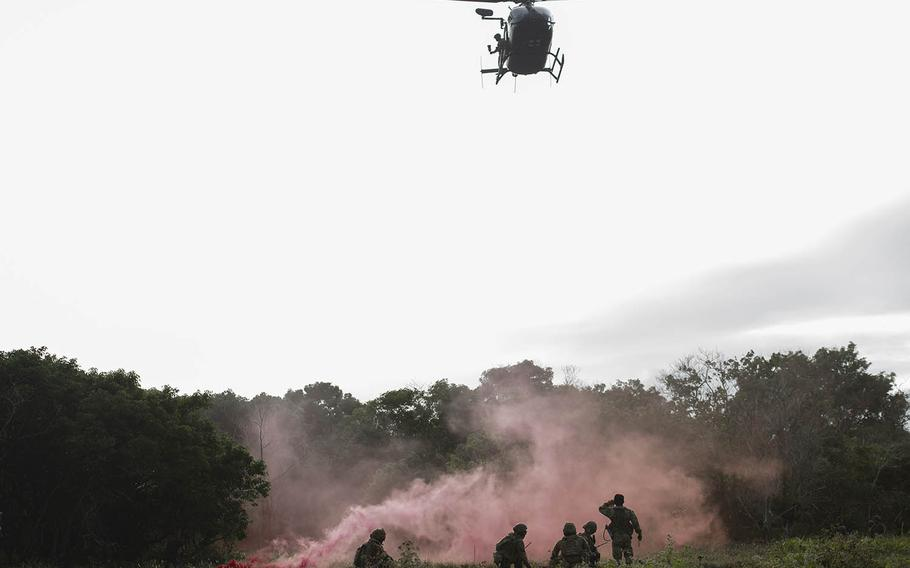 Airmen await a Guam Army National Guard medical helicopter during an exercise at Northwest Field, Guam, Jan. 13, 2021.