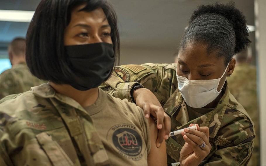 Staff Sgt. Shakeyla Moses administers one of the first Moderna coronavirus vaccines at Yokota Air Base, Japan, Dec. 28, 2020.