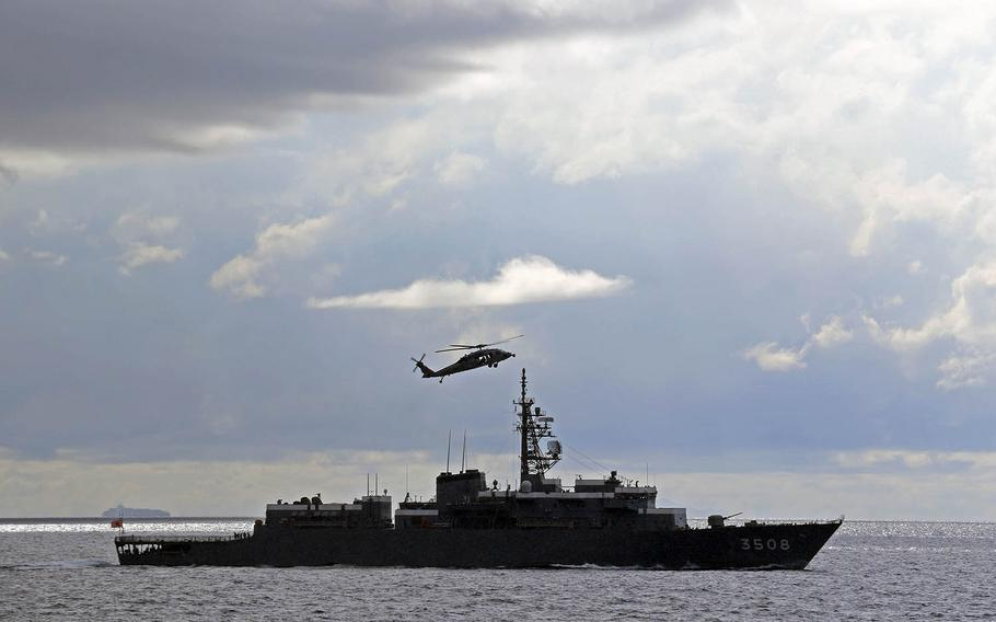 A Navy MH-60S Seahawk helicopter flies alongside the Japan Maritime Self-Defense Force ship JS Kashima in the South China Sea, June 23, 2020.