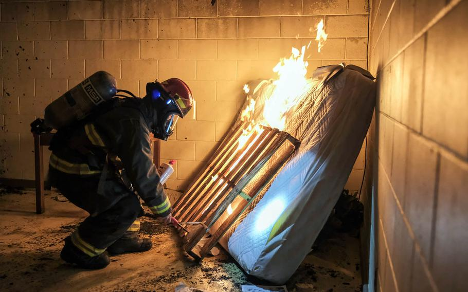 Tech. Sgt. Peter Beyer ignites old furniture inside a condemned dormitory for training at Osan Air Base, South Korea, Jan. 22, 2021.