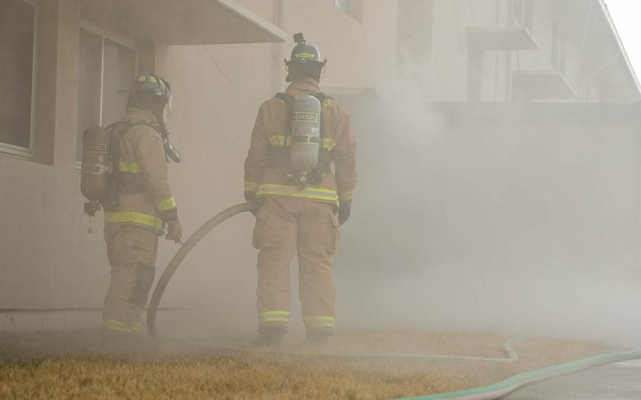 Firefighters with the 51st Fighter Wing guide a firehose for teammates inside a burning dormitory during training at Osan Air Base, South Korea, Jan. 22, 2021.