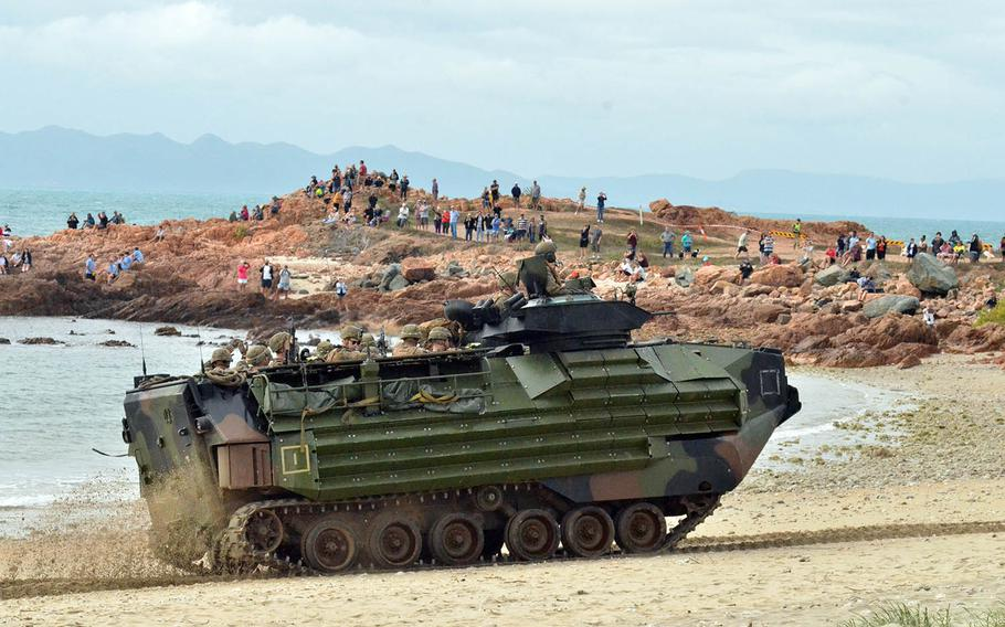Locals watch U.S. Marines move along Kings Beach, Australia, in an assault amphibious vehicle during a Talisman Sabre drill, July 22, 2019.