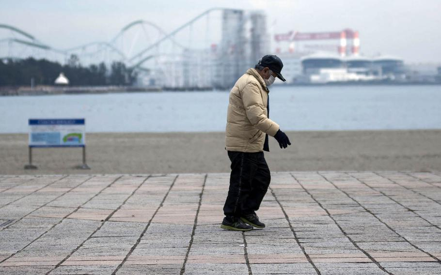 A man wears a mask to guard against the coronavirus while walking in Yokohama, Japan, Jan. 26, 2021.