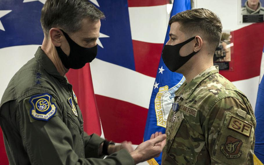 Staff Sgt. Seth Shannon receives the Air Force Achievement Medal from Lt. Gen. Kevin Schneider, commander of U.S. Forces Japan, at Yokota Air Base, Japan, Thursday, Jan. 28, 2021. Shannon was honored for his efforts to bring military working dogs to Japan during the pandemic.