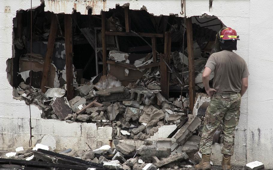 An airman stands outside a fire-gutted warehouse at Kadena Air Base, Okinawa, June 23, 2020.