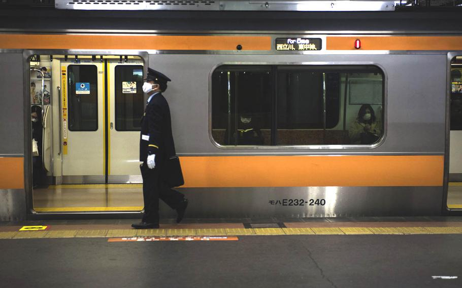 A commuter train prepares to depart Hachioji Station in western Tokyo, Tuesday, Feb. 2, 2021.