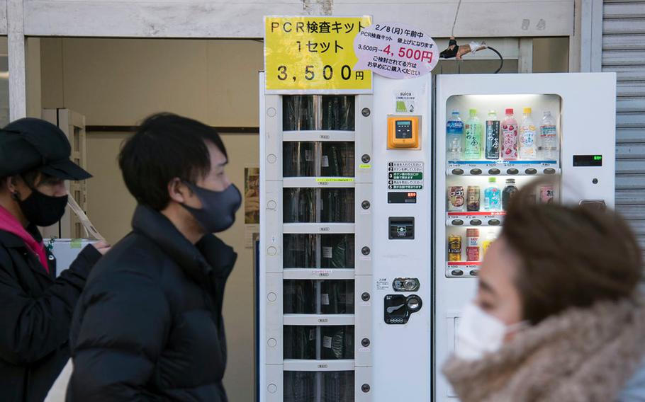 People walk past a vending machine selling polymerase chain reaction kits, which test for the coronavirus, near Ofuna Station in Kanagawa prefecture, Japan, Thursday, Feb. 4, 2021.