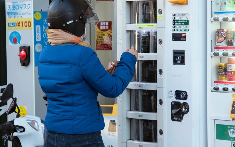 A woman buys a polymerase chain reaction kit, which test for the coronavirus, from a vending machine near Ofuna Station in Kanagawa prefecture, Japan, Thursday, Feb. 4, 2021.