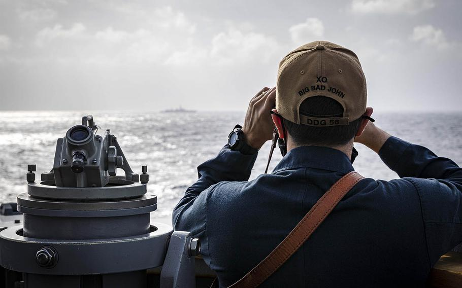 Cmdr. Joseph Gunta, executive officer of USS John S. McCain, observes a surface contact as the the guided-missile destroyer steams near the Paracel Islands in the South China Sea, Friday, Feb. 5, 2021.