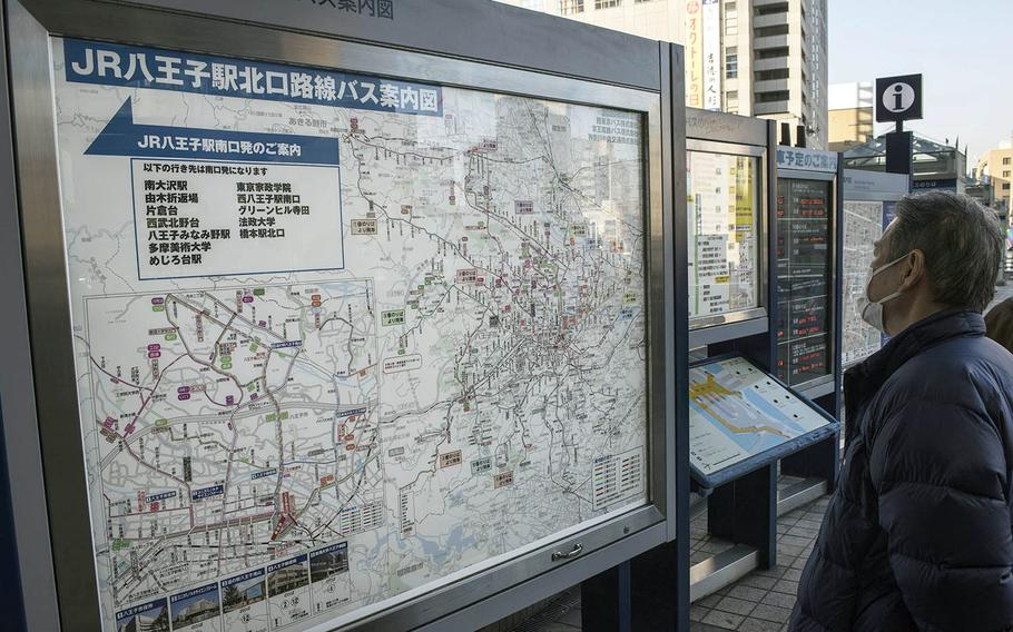 A masked visitor scans a map outside the train station in Hachioji, Japan, Feb. 2, 2021.