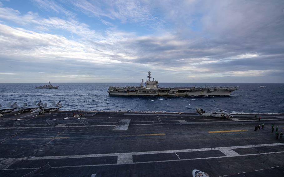 The aircraft carrier USS Theodore Roosevelt, foreground, steams alongside the aircraft carrier USS Nimitz in the South China Sea, Tuesday, Feb. 9, 2021.