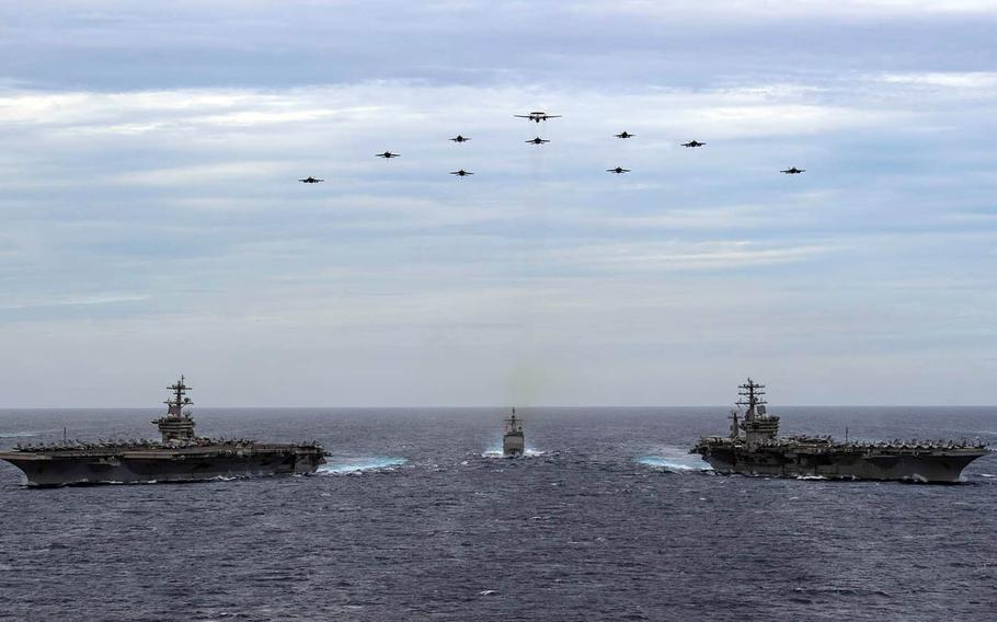 The aircraft carriers USS Nimitz and USS Theodore Roosevelt, along with ships and aircraft from their strike groups, stream through the South China Sea, Feb. 9, 2021.