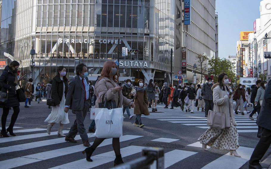People wear masks as they cross the Shibuya Scramble in central Tokyo, Feb. 4, 2021.