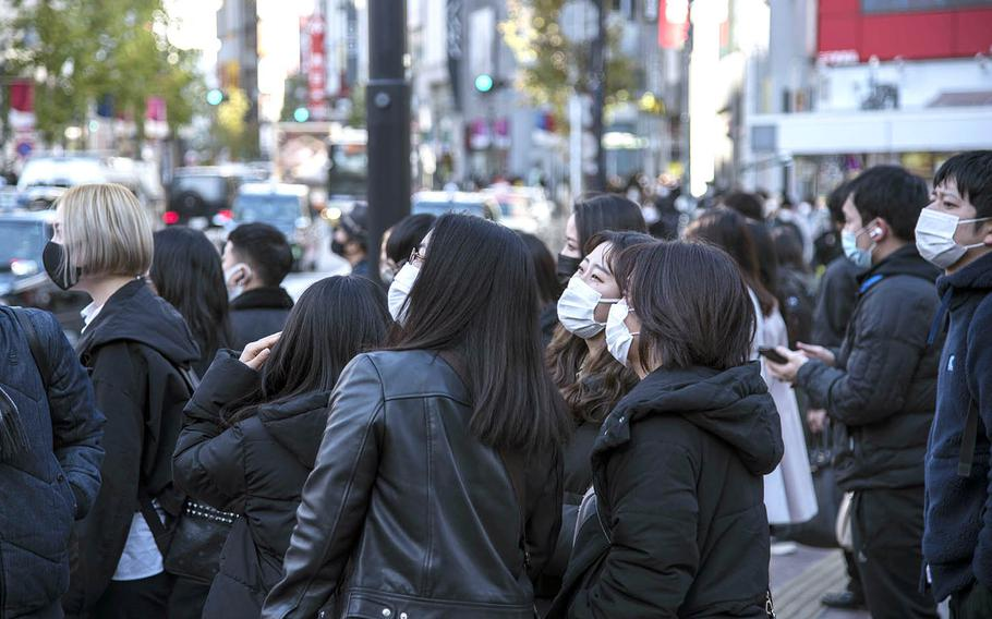 People wear masks as they stroll the crowded streets of Tokyo's Shibuya district, Feb. 4, 2021.