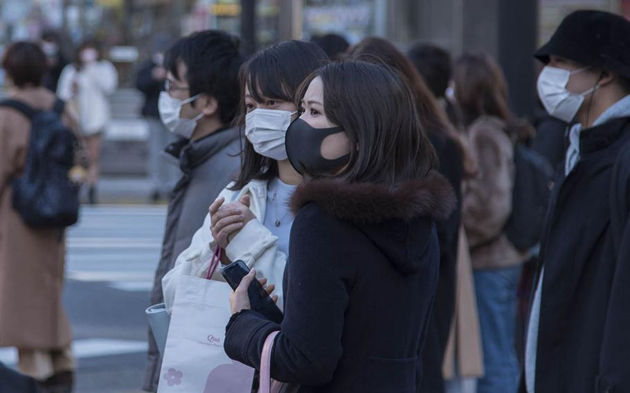 Pedestrians wearing masks as protection against the coronavirus wait to cross a street in central Tokyo, Feb. 4, 2021.