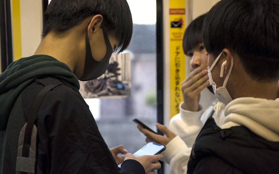 Young men wear masks as protection against the coronavirus while riding a train this month in western Tokyo.
