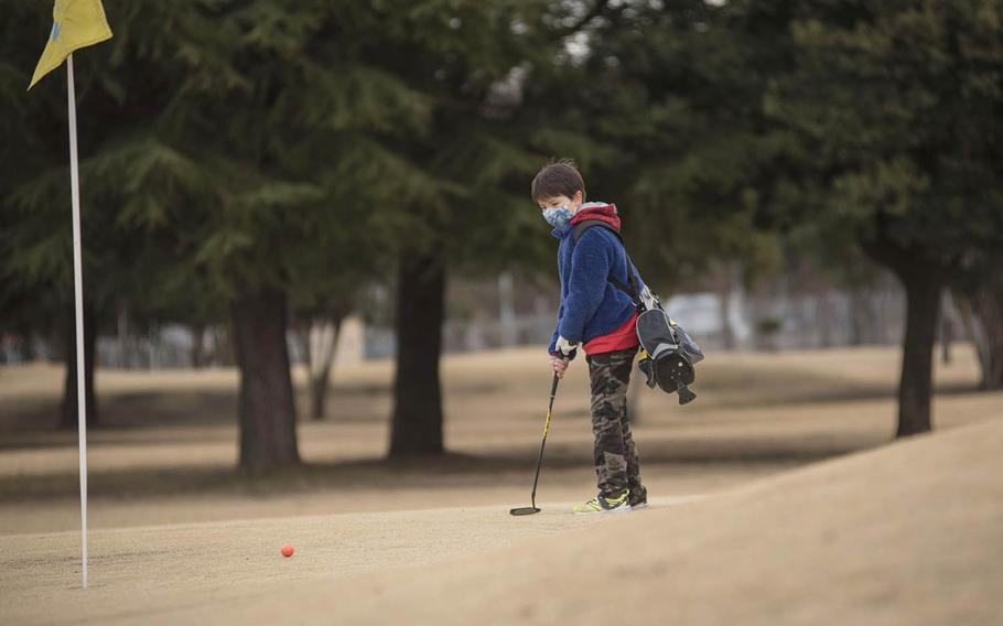 Junior golfer Jake Hughes putts on the Par 3 golf course at Yokota Air Base, Japan, Thursday, Feb. 18, 2021.