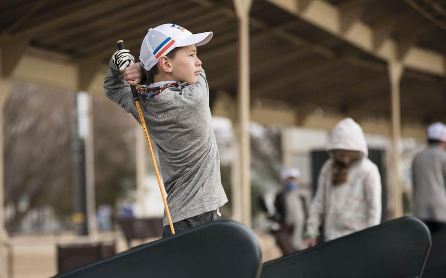 Junior golfer Ethan Kliber tees off on the driving range at Yokota Air Base, Japan, Thursday, Feb. 18, 2021.