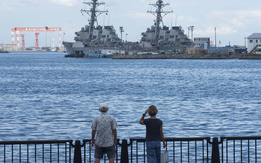 People check out U.S. Navy warships docked at Yokosuka Naval Base, Japan, Aug. 27, 2020.