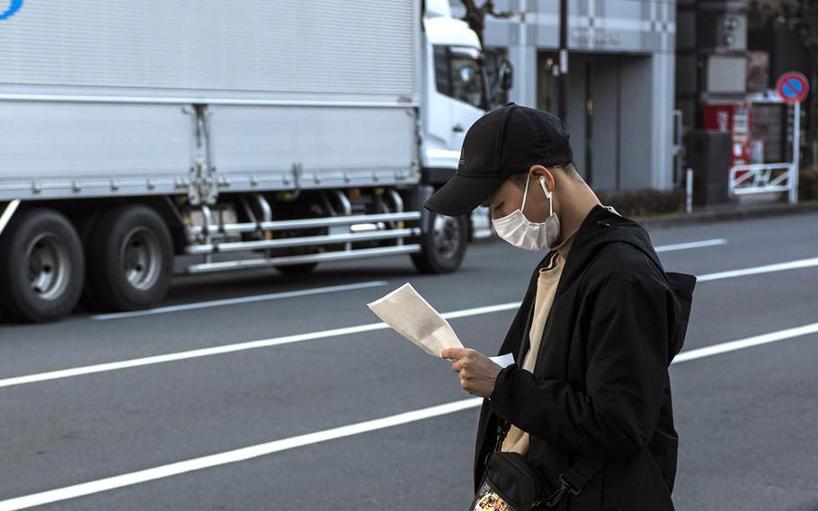 A  man wearing a mask as protection against the coronavirus pauses on a street in Hachioji, Japan, Feb. 2, 2021.