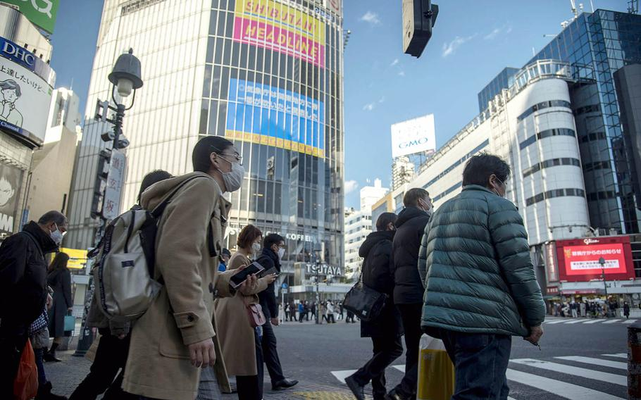 Masked pedestrians prepare to cross the busy Shibuya Scramble intersection in central Tokyo, Feb. 4, 2021.