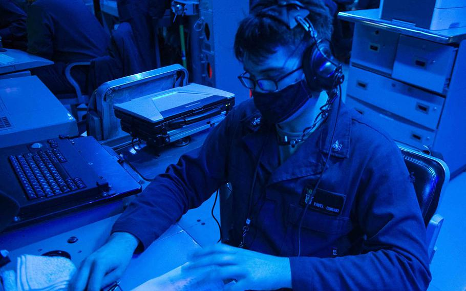 Petty Officer 2nd Class Pavel Gorski, a fire controlman from St. Petersburg, Fla., writes in a watch log as the guided-missile destroyer USS Curtis Wilbur passes through the Taiwan Strait, Tuesday, Feb. 23, 2021.